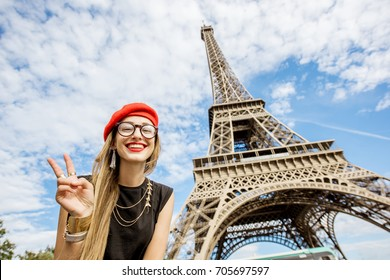 Portrait of a young and happy woman tourist in red hat near the Eiffel tower in Paris