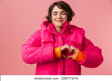 Portrait of young happy woman in warm coat with making heart gesture and smiling isolated over pink background