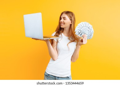 Portrait of a young happy woman wearing a white t-shirt, using a laptop laptop and holding money in hand, on yellow background