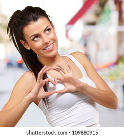 portrait of a young healthy girl gesturing a heart symbol at a street
