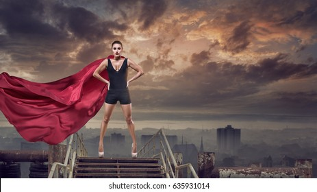 Portrait of young hero woman with super person red cape guard city