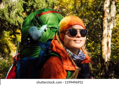 Portrait of young hiker in colorful fantastic forest landscape at gold autumn
