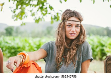 Portrait of young hippie girl with long hair and headband looking at camera