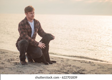 portrait of the young hipster with black labrador dog in the morning on the beach