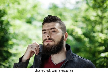 portrait of a young hipster with green natural background behind