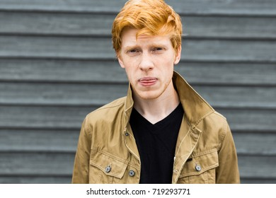 portrait of a young hipster male man with red hair dressed in jeans sneakers hickey jacket, on a wall background emotional portrait smile cheerful mood