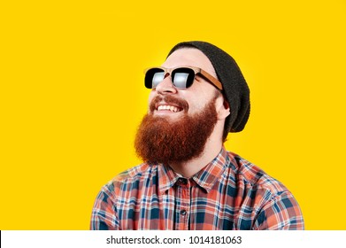 Portrait of young hipster man in sunglasses and hat posing on yellow background. Smiling bearded man wearing sunglasses, studio shot. Happy man with beard looking up.
