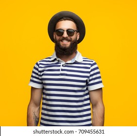 Portrait of young hipster man in sunglasses and hat posing on orange background smiling at camera.