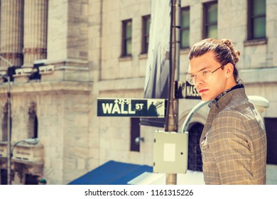 Portrait of Young Hispanic American Male College Student in New York City, with hair bun, wearing glasses, dressing in brown patterned jacket, standing on Wall Street, thinking, lost in thought.