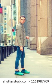 Portrait of Young Hispanic American Male College Student in New York City, wearing glasses, brown patterned jacket, blue jeans, green patterned sneakers, standing on old style street, looking away.