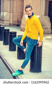 Portrait of Young Hispanic American Man in New York City, wearing glasses, yellow long sleeve T shirt, blue jeans, green patterned sneakers, small black scarf around neck, sitting on pillar on street.