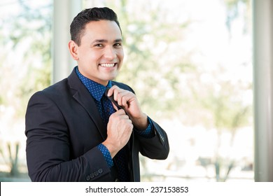 Portrait of a young Hispanic businessman fixing his tie and smiling