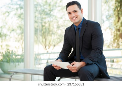 Portrait of a young Hispanic businessman using a tablet computer for work and smiling