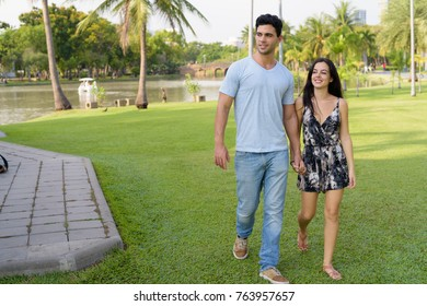 Portrait of young Hispanic couple relaxing in the park together