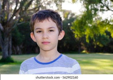 Portrait young hispanic or latino boy outdoor in park, with sad serious thoughtful facial expression, copy space, blurred background.