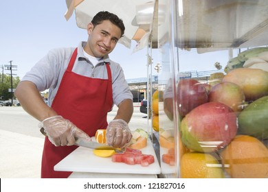 Portrait of young hispanic male street vendor chopping fruits on board