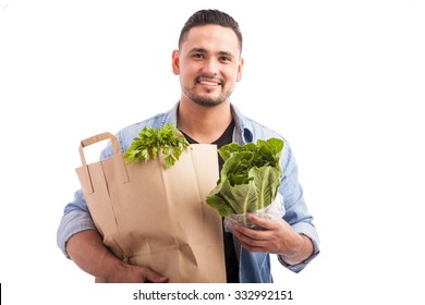 Portrait of a young Hispanic man carrying a bag of groceries with a lot of green in it against a white background