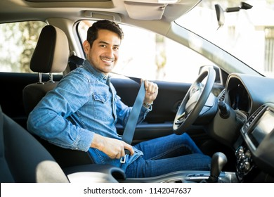 Portrait of young hispanic man sitting in driving seat of car, fastening safety belt and making en eye contact