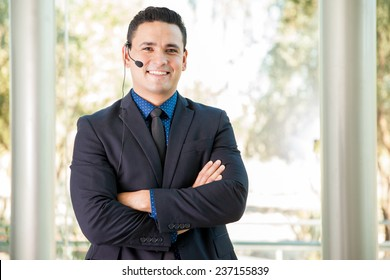 Portrait of a young Hispanic man wearing a suit and a headset in a call center