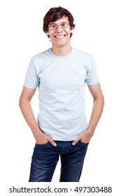 Portrait of young hispanic man wearing glasses, blue t-shirt and jeans standing with hands in pockets and smiling isolated on white background