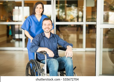 Portrait of a young Hispanic patient leaving the hospital in a wheelchair after a full recovery
