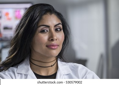 Portrait of a young hispanic woman in a lab coat