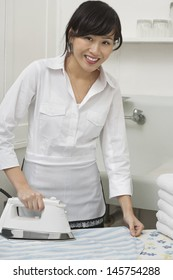 Portrait of young housemaid ironing shirt