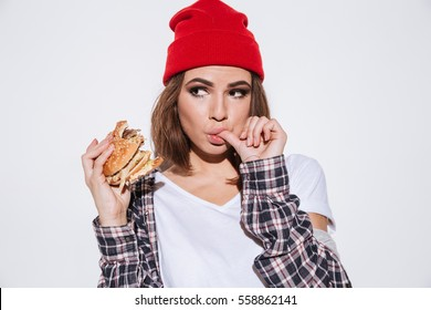 Portrait of young hungry woman dressed in shirt in a cage print wearing hat standing isolated over white background and eating burger