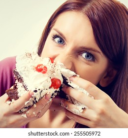 Portrait of young hungry woman eating pie