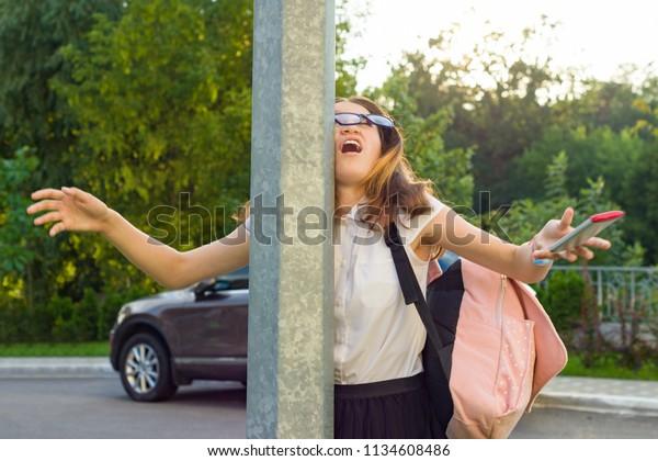 携帯電話に気を取られた若い無愛想な女の子のポートレート。女の子が街路に衝突し、電話を落とした