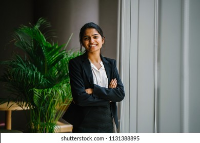 Portrait of a young Indian Asian business woman standing by the window in a meeting room, smiling with her arms crossed. She looks confident, happy and optimistic.
