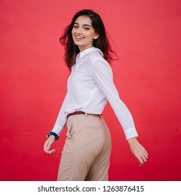 A portrait of a young Indian Asian girl business student dressed in a crisp white shirt and khaki pants. She is beautiful, tall, elegant and professional.