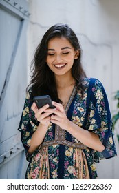 Portrait of a young Indian Asian millennial woman checking her smartphone. She is wearing a summer floral dress and is smiling / laughing happily.