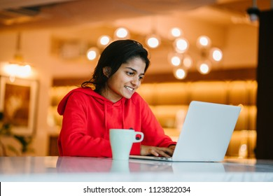 Portrait of a young Indian Asian student woman typing and working on her notebook laptop in a coffee shop during the day. She is wearing a comfortable red sweater and enjoying a cup of coffee.