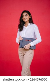 Portrait of a young Indian Asian student girl in a white shirt and khaki pants with her laptop and a notebook. She is beautiful, tall and elegant.