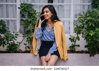 Portrait of a young Indian Asian woman talking on her smartphone as she leans against a stone bench during the day. She is attractive, beautiful and smiling as she speaks.
