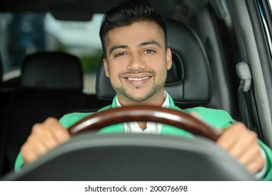 Portrait of young Indian business man, driving a car