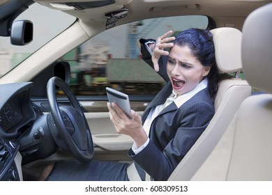 Portrait of a young Indian businesswoman driving a car while using a mobile phone and looks closing her face before car accident