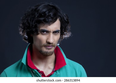 Portrait of young Indian man against black background