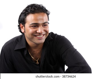 A portrait of a young Indian man wearing a black shirt and gold chain, on white studio background.