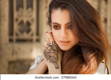 Portrait of a young indian woman in casual style with mehendi on the streets of old city