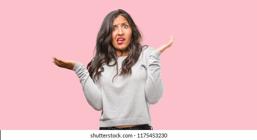 Portrait of young indian woman crazy and desperate, screaming out of control, funny lunatic expressing freedom and wild
