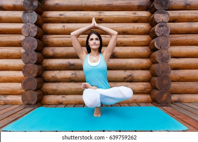 Awesome Portrait Of Young Indian Woman Working Out, Doing Butterfly Yoga Pose On Wooden  Terrace.