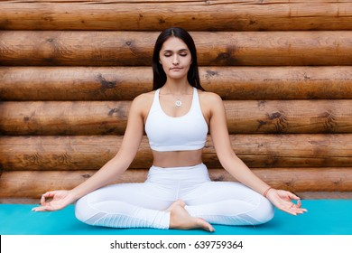 Portrait Of Young Indian Woman Working Out, Doing Butterfly Yoga Pose On Wooden  Terrace.