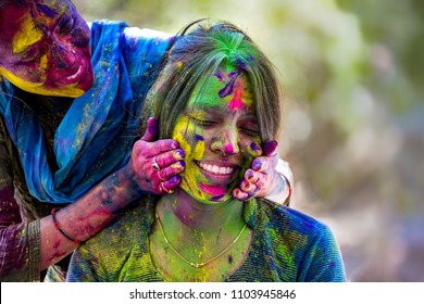 Portrait Of Young Indian Women With Colored Face celebrating Holi Color festival