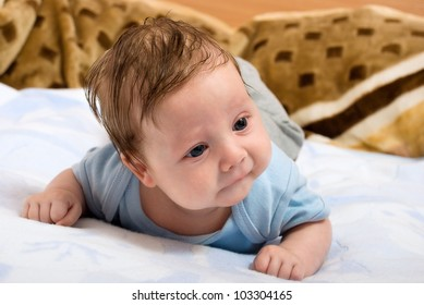 Portrait of young infants lying on his stomach and looking at the camera.