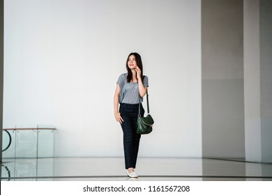 Portrait of a young Japanese Asian woman talking on her smartphone and walking in a clean, modern and futuristic mall. She is comfortably dressed in loose clothing with a sling bag.