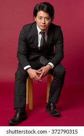 A portrait of a young Japanese man in a business suit sitting on a stool in a cool pose.