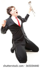 Portrait of young jazz man joy, glee and his trumpet white background