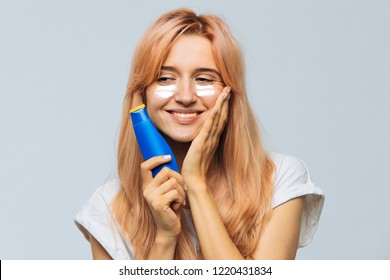 Portrait of young joyful cute woman smiling and applying suntan cream (sunscreen lotion) on face. Pretty female smeared face, cheeks with sun protection cream. Sunburn, vacation, sun concept